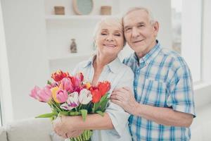 older couple hugging with flowers in granny flat