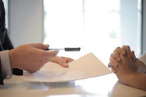 hand holding pen passing property law contract to property lawyer
